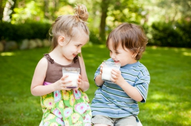Two Little Kids Drinking Milk While Outdoors